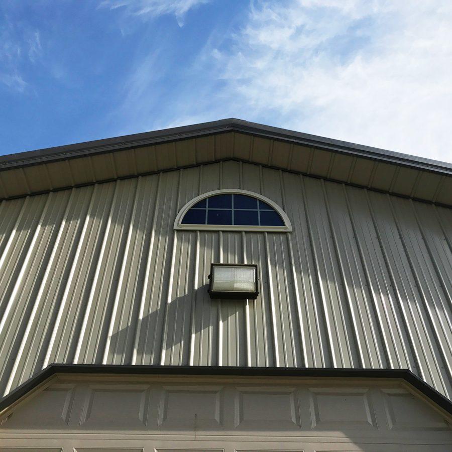 tan metal overhang and small half moon window